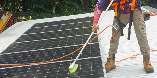 Solar energy specialist cleans and maintains solar panels on roof